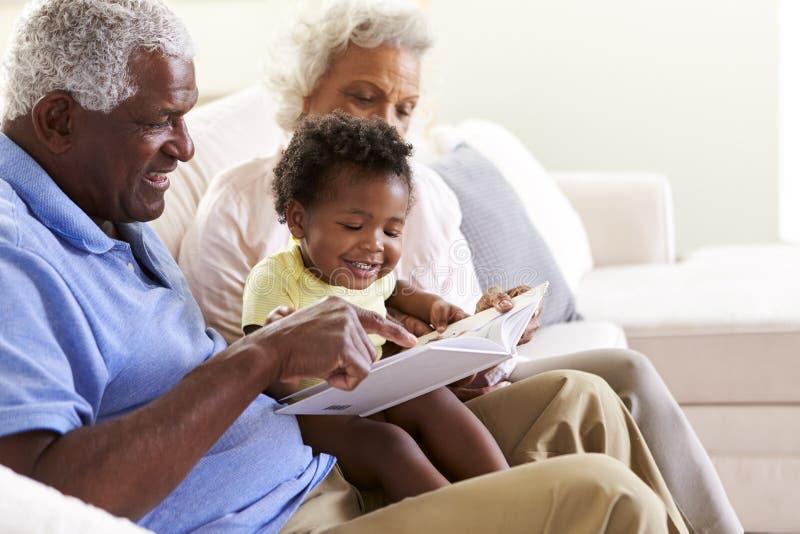 Morföräldrar som tillsammans sitter på den Sofa At Home With Baby sondotterläseboken arkivbilder