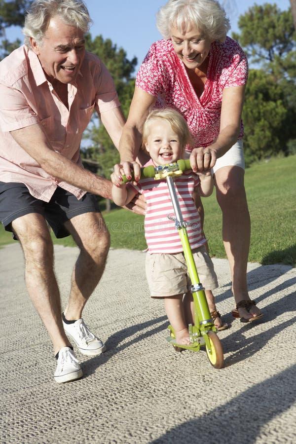 Morföräldrar som undervisar sondottern att rida sparkcykeln parkerar in royaltyfria bilder