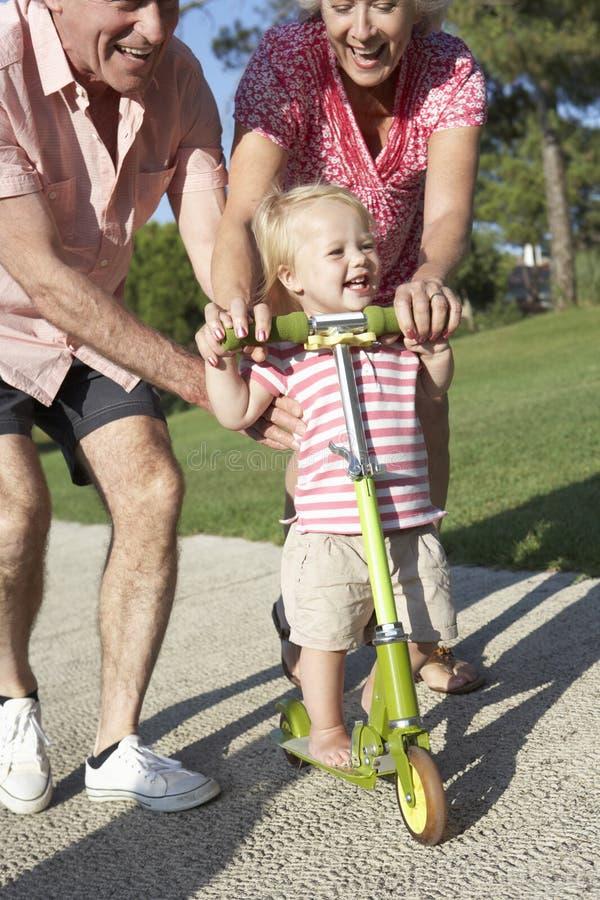 Morföräldrar som undervisar sondottern att rida sparkcykeln parkerar in fotografering för bildbyråer