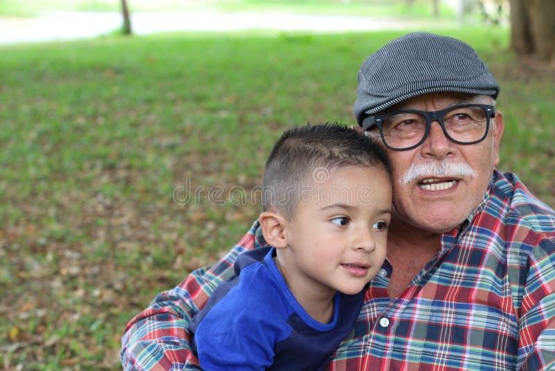 Morfar som berättar berättelser till sonsonen arkivfoto