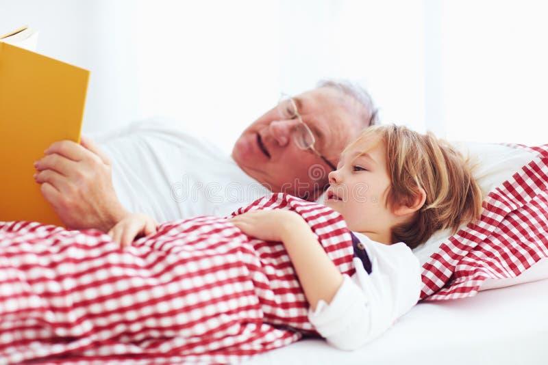 Morfar som läser en bok till hans barnbarn i säng fotografering för bildbyråer