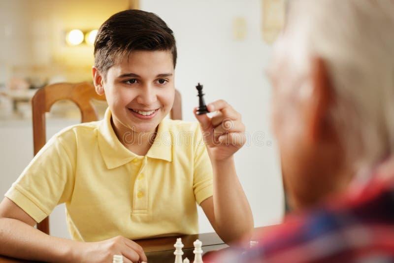 Morfar som spelar schackbrädeleken med den hemmastadda sonsonen royaltyfri foto