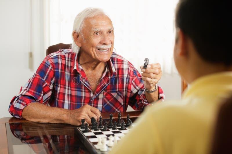 Morfar som spelar schackbrädeleken med den hemmastadda sonsonen arkivbilder