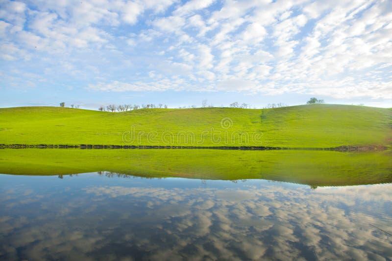 Morgen auf dem See mit grünen Hügeln und Reflexion stockbilder
