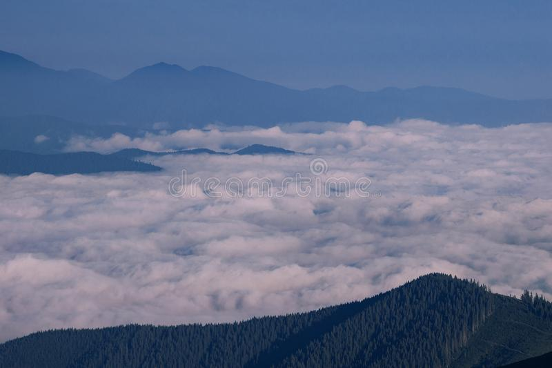 Morgen in den Bergen über weißen Wolken stockbild