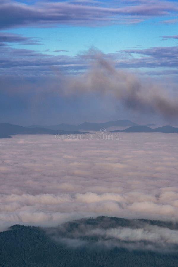 Morgen in den Bergen über weißen Wolken stockbilder