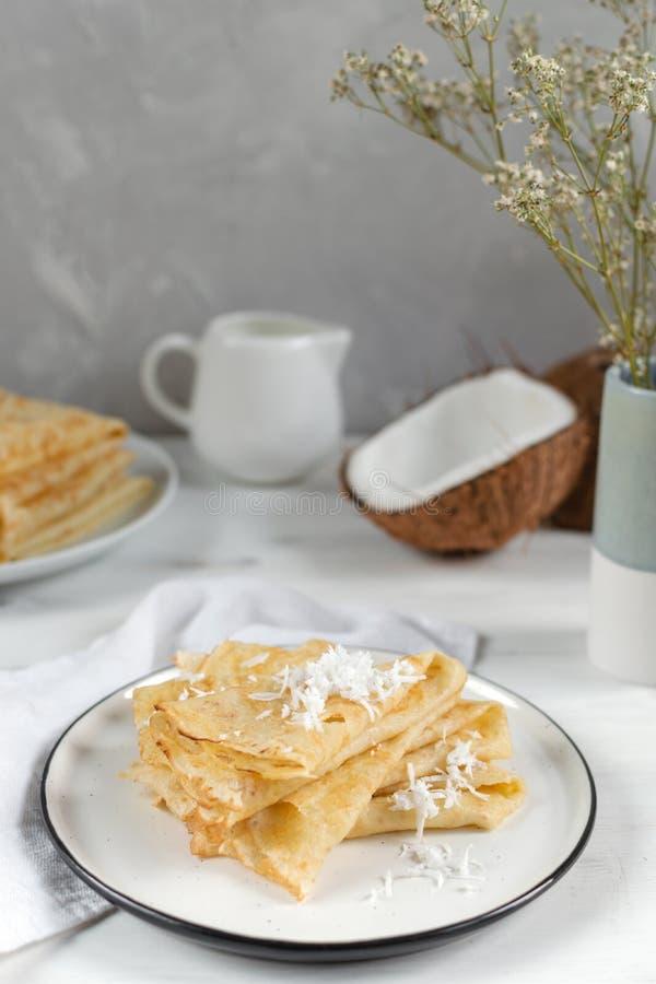 Morgen, Frühstück - traditionelle russische Blinipfannkuchen, französische Krepps, frische Kokosnuss, Milchflasche, weißer ke stockfotografie