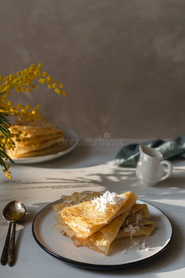 Morgen, Frühstück - traditionelle russische Blinipfannkuchen, französische Krepps Schlagsahne, Mimosenblume stockfoto