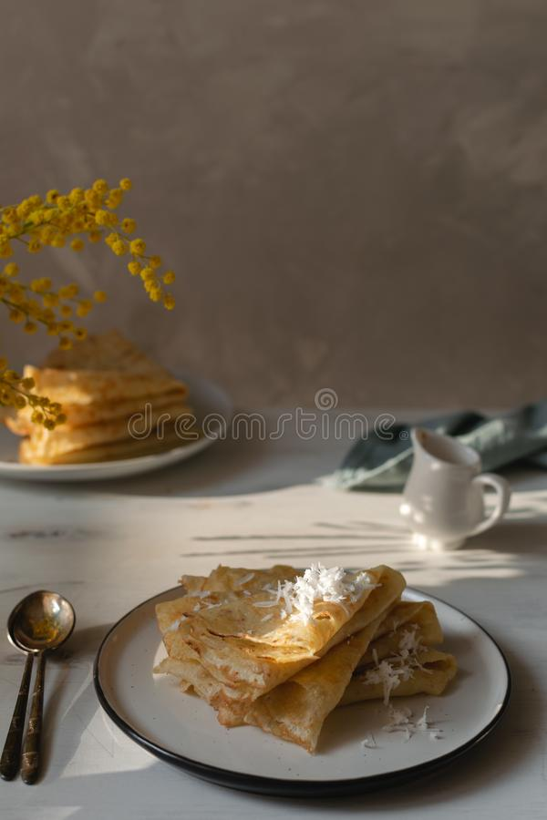 Morgen, Frühstück - traditionelle russische Blinipfannkuchen, französische Krepps Schlagsahne, Mimosenblume lizenzfreies stockfoto