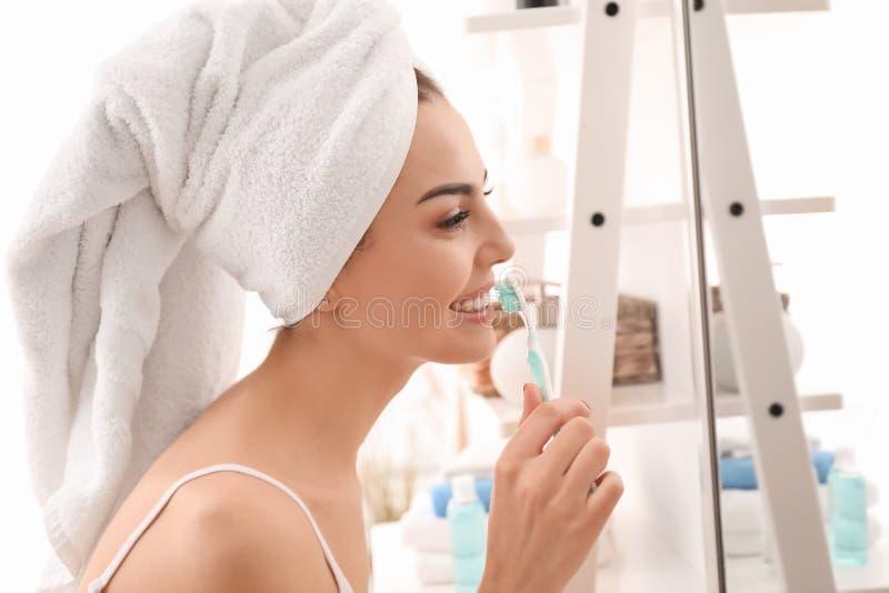 Morgen von schönen Reinigungszähnen der jungen Frau im Badezimmer stockbilder