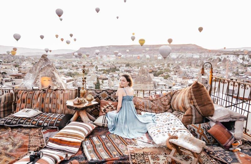 Morgenansicht in Cappadocia Terrassenansicht in Goreme-Frau mit Heißluftballonen und -teppichen stockbild