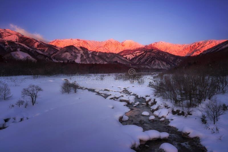Morgenansicht von Fluss Hakuba Miyama und von rotem Berg Schnee herum drei Berge Hakuba-Präfektur Nagano, Japan Ushiro- lizenzfreie stockfotografie