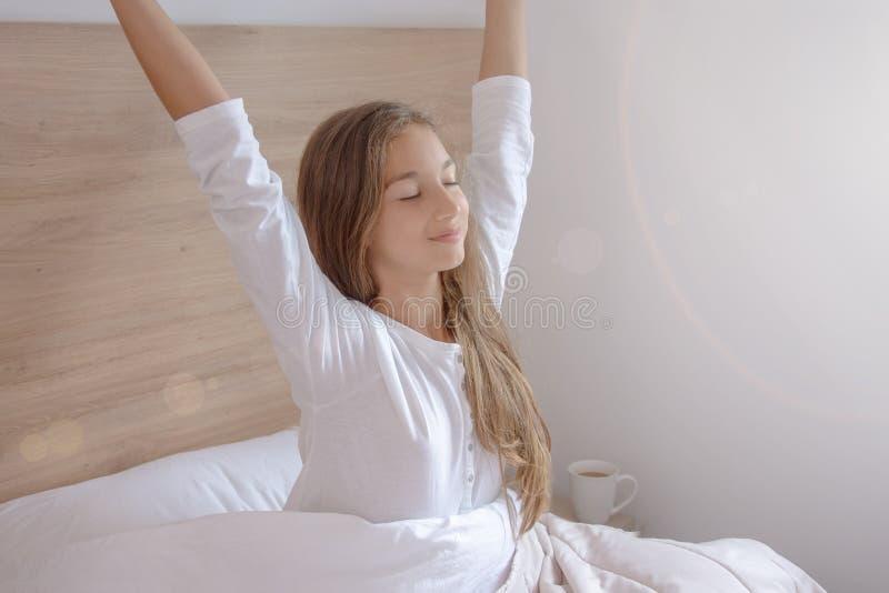 Morgenausdehnung auf dem Bett am Fenster zu Hause lizenzfreie stockbilder