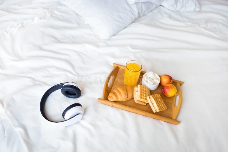 Morgenfrühstück auf dem weißen Bett Tray Croissant Coffee Waffles Juice lizenzfreie stockfotos