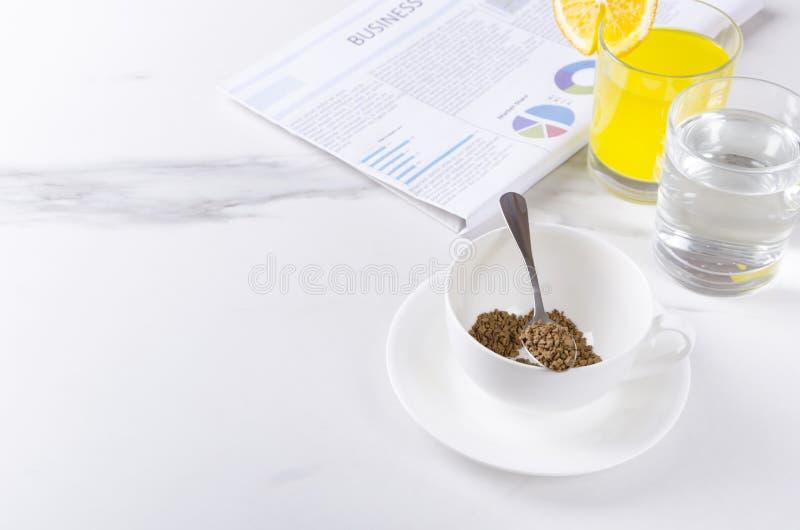 Morgenfrühstück mit frischer Zeitung Instantkaffee, Glas Wasser und Orangensaft Konzept breakfastEmpty Raumes f des Geschäfts stockfotos