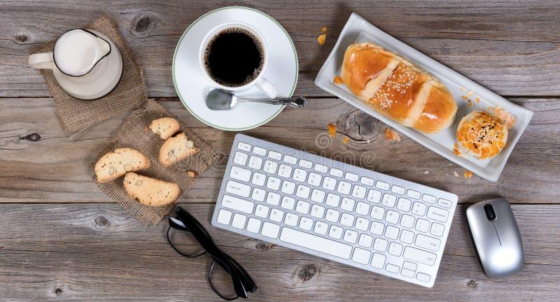 Morgengebäckmahlzeit und -kaffee mit Computertechnologie auf rusti lizenzfreies stockbild