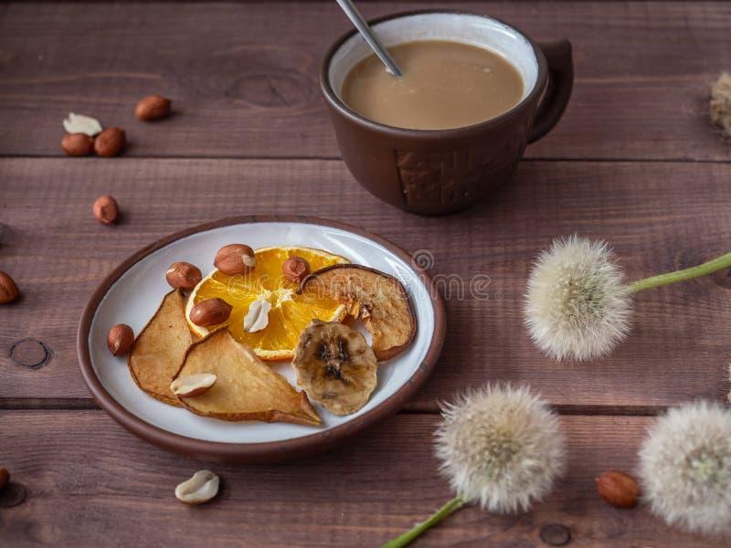 Morgenimbiß mit Fruchtchips und Kaffee für Eignungsmädchen, flaumiger Löwenzahn für eine gute Laune stockfoto