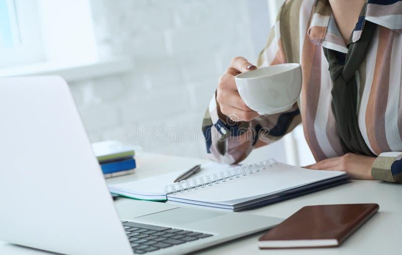 Morgenkaffee vor einem produktiven Arbeitstag Junger weiblicher Büroangestellter, der Kaffeetasse hält und den Laptop betrachtet lizenzfreie stockfotografie