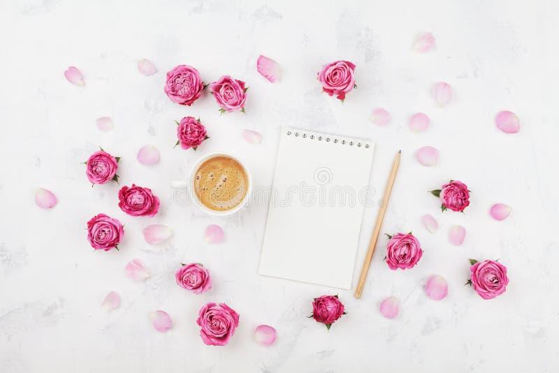 MorgenKaffeetasse für Frühstück, leeres Notizbuch, Bleistift und Rosarose blüht auf weißer Steintischplatteansicht in Ebenenlagea lizenzfreies stockbild