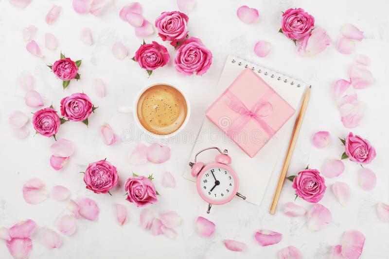 MorgenKaffeetasse, Geschenkbox, Wecker und Rosarose blüht auf weißer Tischplatteansicht in Ebenenlageart glückliches neues Jahr 2 stockfoto