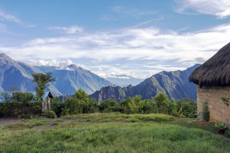 Morgenlandschaft mit peruanischen Anden-Gebirgsspitzen und Stroh überdachtem kleinem Haus bei Sonnenaufgang stockbilder