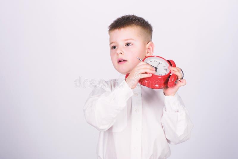 Morgenprogramm Sch?ler mit Wecker Hemdes des Kinderrote Fliege des entz?ckenden Jungen wei?en Entwickeln Sie Selbstdisziplin Ganz stockbilder