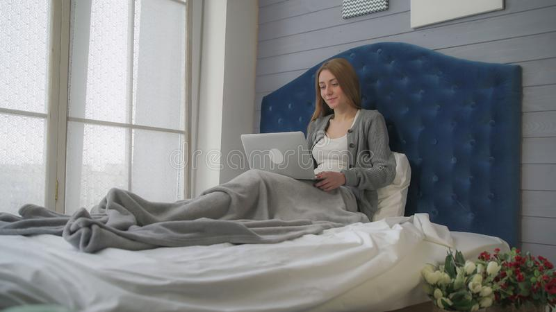 Morgenreise, Mädchen im Bett sprechend mit einem Laptop stockbild