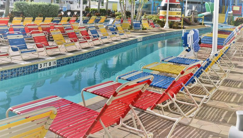 Morgenruhe, in der leere bunte Strandstühle durch das Pool in Florida ausgerichtet werden, das den Mangel an Touristen darstellt lizenzfreie stockbilder