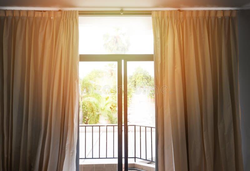 Morgens des Schlafzimmerfensters/Sonnenlicht durch in den offenen Vorhängen des Raumes mit Balkon lizenzfreie stockfotografie