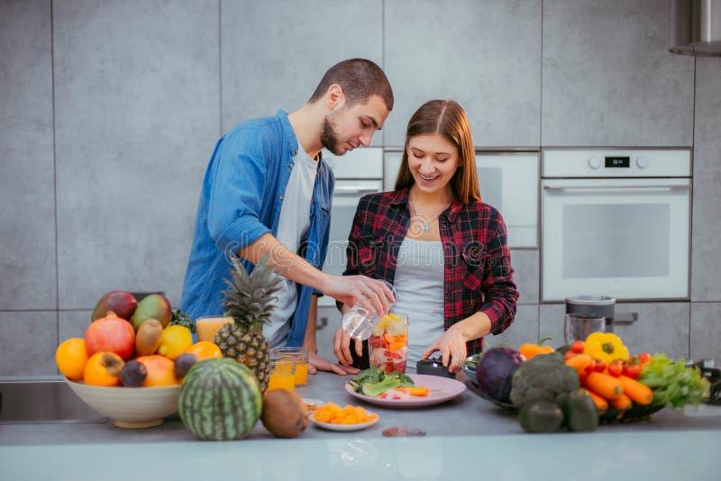 Morgens ein charismatisches Paar der modernen Küche, das einen frischen Smoothie zum das Frühstück macht stockbilder
