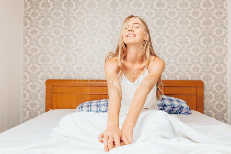 Morgens ein schönes Mädchen im Schlafzimmer, das und r aufwachte lizenzfreie stockfotos
