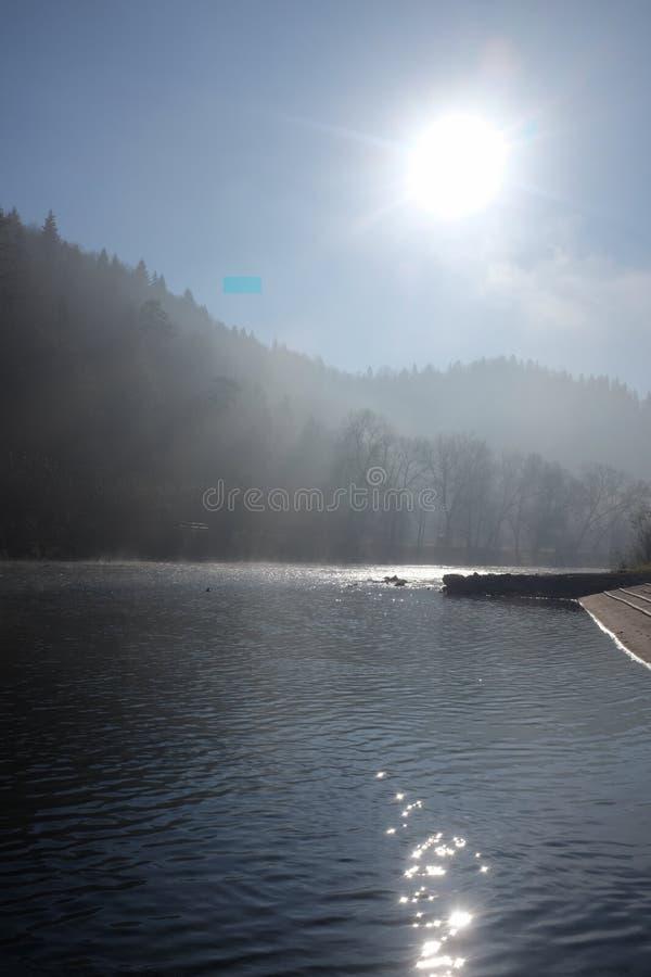 Morgensonne und -nebel, die über einem Gebirgsfluss schweben stockfotos