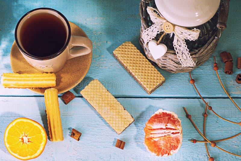 Morgenszene mit Tasse Tee oder Kaffee, niederländisches Plätzchen stroopwafel, blaue Andenken Delfts, auf blauer Tabelle lizenzfreies stockbild