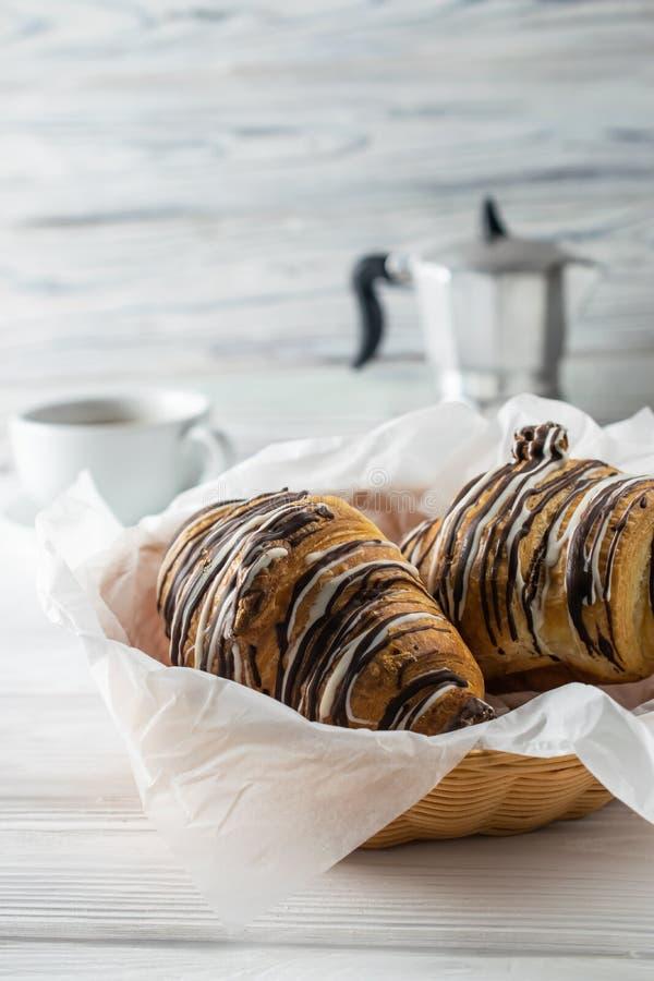 Morgentabelle mit Kaffee, frisch gebackene Hörnchen mit Schokolade stockfotografie