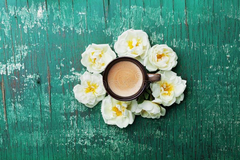 Morgentasse kaffee und schöne Rosen blüht auf rustikaler Tischplatteansicht der Knickente Gemütliche Frühstücks-Ebenenlageart lizenzfreie stockfotografie