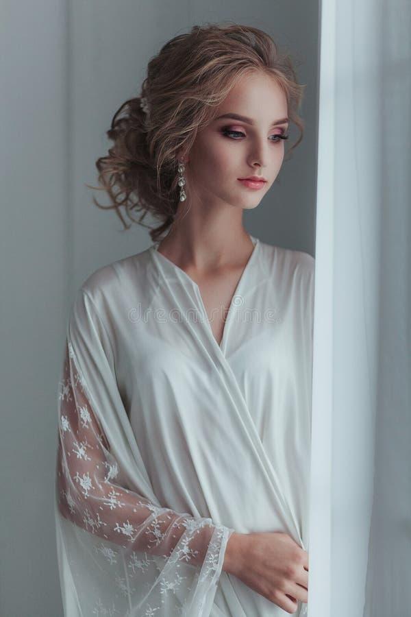 Morgon av bruden Härlig ung kvinna i elegant vit ämbetsdräkt med anseende för modebröllopfrisyr nära arkivfoto