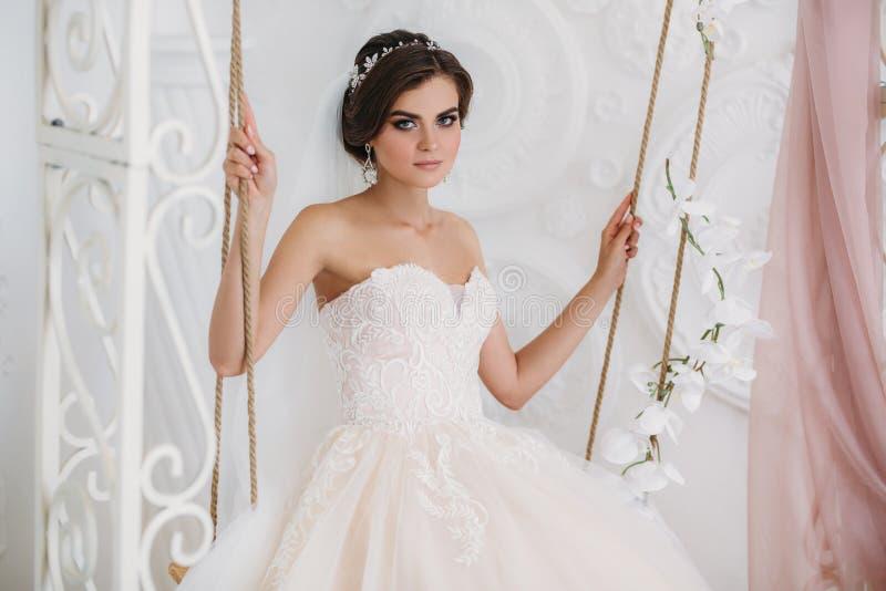 Morgon av bruden Stående av den härliga kvinnan i den vita lyxiga bröllopsklänningen med brud- makeup och frisyren arkivfoto