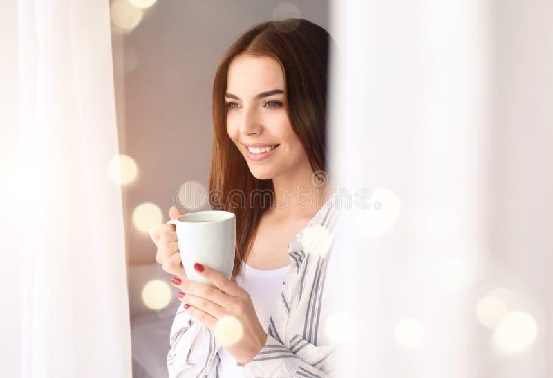 Morgon av den härliga unga kvinnan som hemma dricker kaffe arkivbild