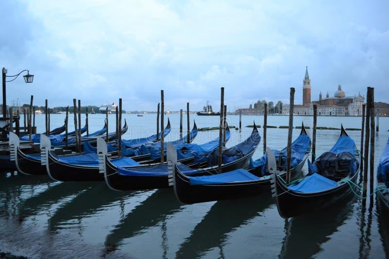 Morgon för vår för Venedig lagun tidig på gryning och blåa gondoler som ankras på sjösidan royaltyfri foto