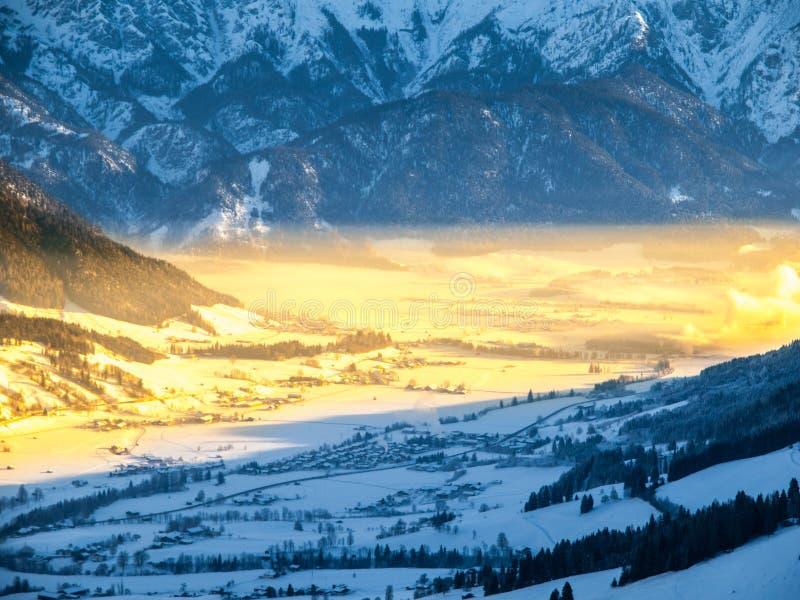 Morgon i den alpina dalen Övervintra ogenomskinlighet som är upplyst vid strålen av resningsolen, Leogang, Österrike royaltyfria foton
