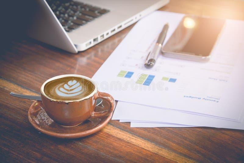 Morgonarbetsplats: kopp kaffe med lattekonst- och affärsobjekt arkivbilder