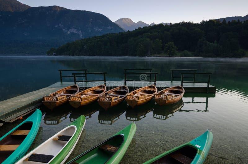 MorgonBohinj sjö med tomma fartyg som binds till pir, Bohinj, Slovenien, Europa royaltyfri foto