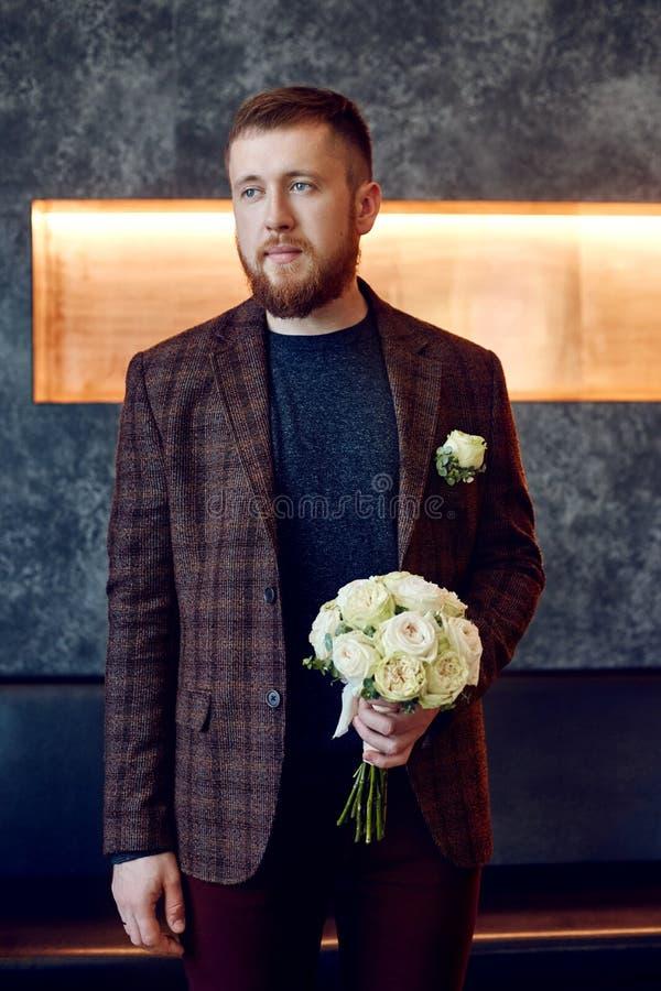 Morgonbrudgum En hipsterman i ett omslag som rymmer en bukett av blommor för hans älskling Härlig skäggig man som förbereder sig  royaltyfri fotografi