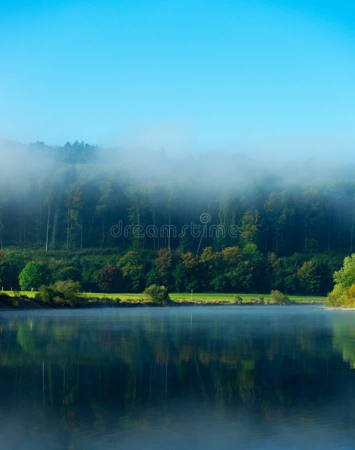 Morgondimma över floden i solsken fotografering för bildbyråer