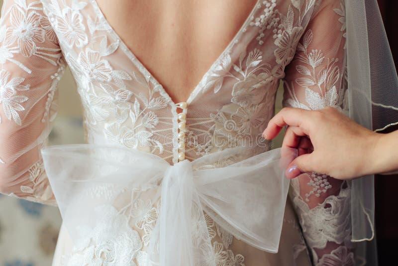 Morgonen av bruden, förbereder sig en härlig kvinna i en vit klänning för bröllopet fotografering för bildbyråer