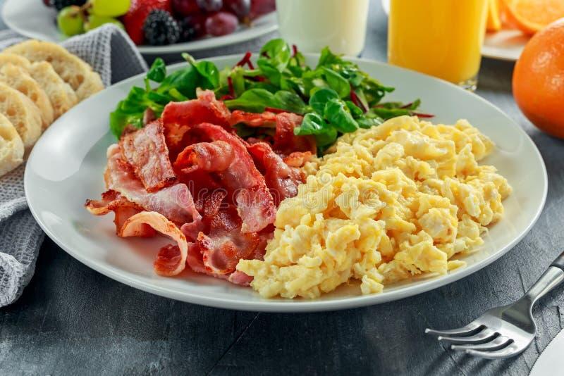 Morgonen förvanskade ägget, baconfrukost med orange fruktsaft, mjölkar, bär frukt, panerar på den vita plattan arkivbild