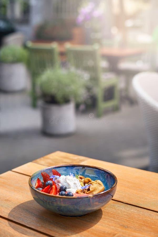 Morgonfrukost i en blå platta på tabellen nya bunkar för frukost för bärblåbärsmoothie av muttrar, frö och royaltyfri fotografi