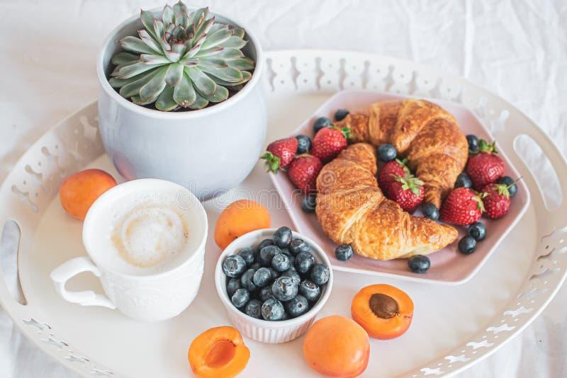 Morgonfrukost i s?ng, kopp kaffe, giffel, nya b?r, kruka med suckulenten royaltyfria bilder
