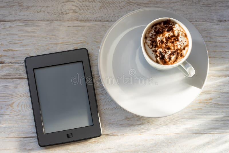 Morgonfrukost med en kopp av kakao och en eBook royaltyfri foto