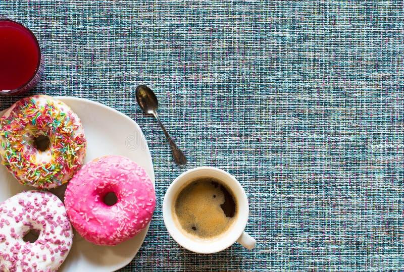 Morgonfrukost med färgrika Donuts och kaffe royaltyfri bild